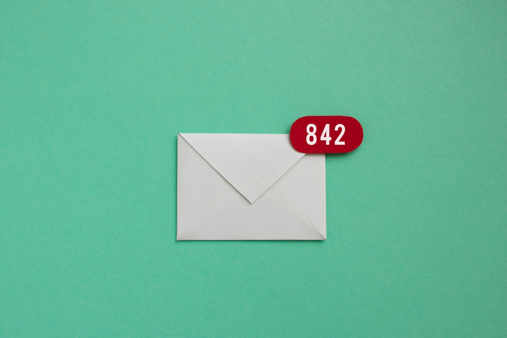 A white paper envelope at the center of a greenpaper. A red notification bubble is at the right upper corner of the envelope. 842 notifications is written on white.