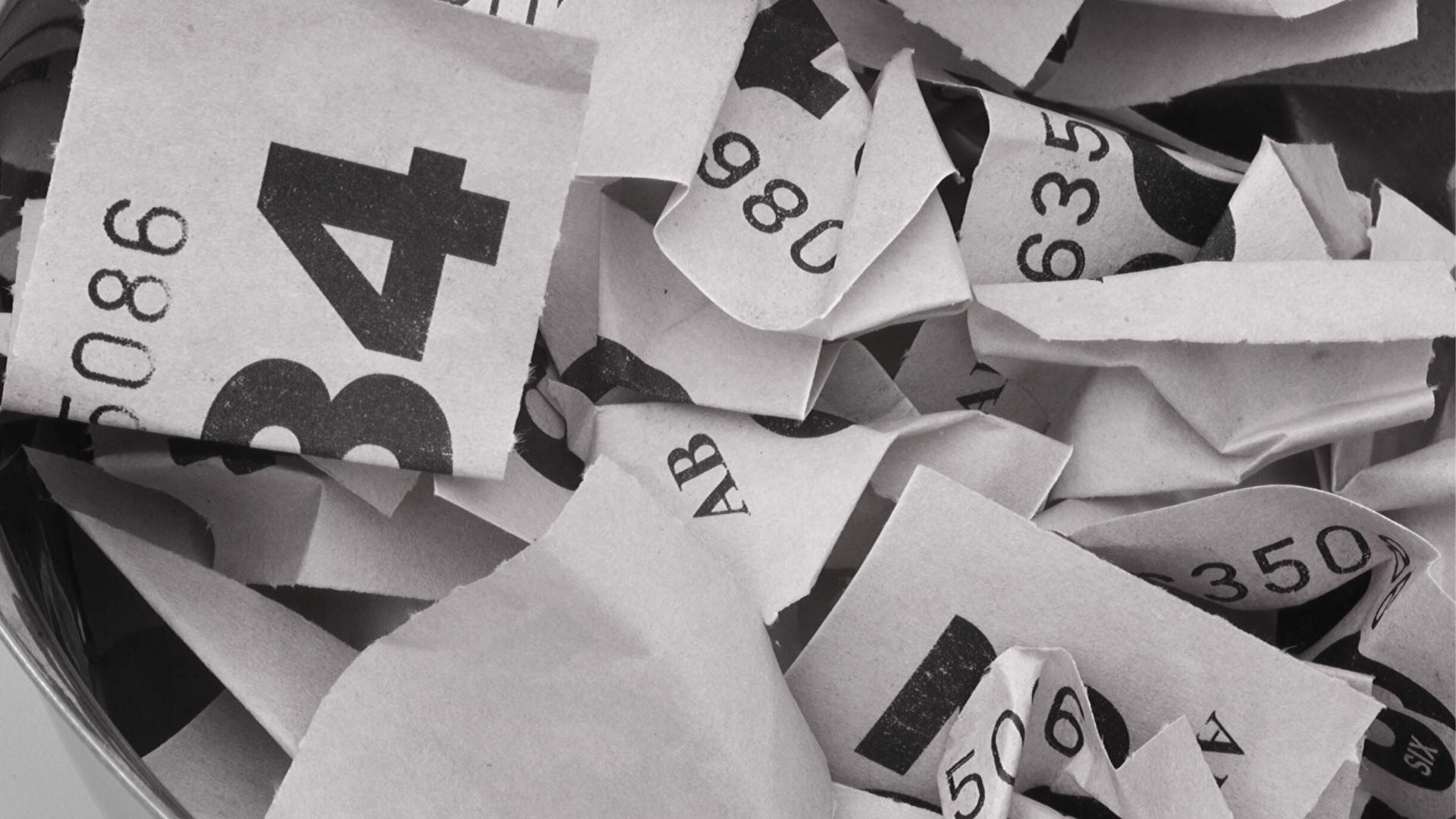 Close-up black and white photo of crinkled queuing tickets